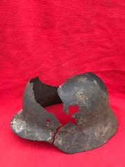 German soldiers M40 helmet with large battle damage,paint work remains recovered from Priekule in the Kurland pocket defended by the SS Nordland Division during the battle