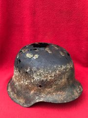 German soldiers M42 steel helmet with green paint remains,white stripe,battle damaged recovered from the Normandy battlefield of 1944