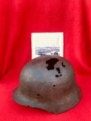 German soldiers M35 steel helmet with some green paint and decal remains recovered in 2009 from Grand Fort Philippe near Calais part of the Atlantic wall
