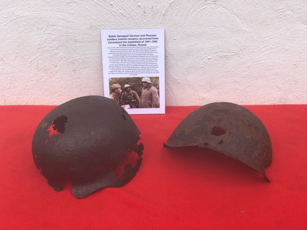 Battle damaged pair of German and Russian soldiers helmets both blown apart relics recovered from Sevastopol the battlefield of the Crimea in 1942