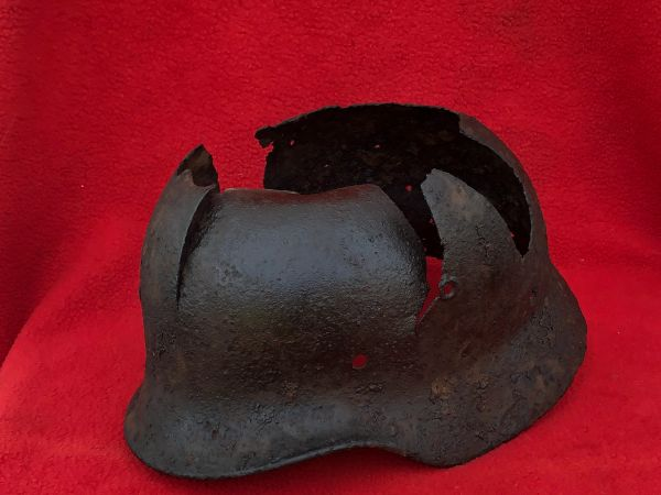 German M40 helmet with paintwork remains,battle damaged used by soldier of the 5th Parachute Division recovered in the forest outside Wiltz on the Belgium-Luxembourg border in the Ardennes Forest battle of the bulge 1944-1945