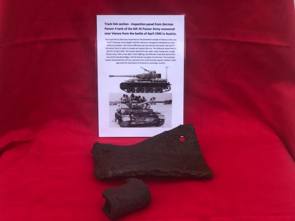 Blown section of winterkette track link and small inspection panel used by German panzer 4 tank of the 6th SS Panzer Army recovered from the battlefield outside Vienna in April 1945