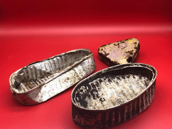 A pair of food tins and a small triangle tin with yellow stamped markings used by German soldiers of 212 Volksgrenadier-Division recovered near town of osweiler, Luxemburg from the battle of the Bulge 1944-1945