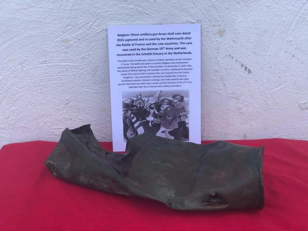 Belgium 75mm artillery gun brass shell case, battle damaged dated 1923 captured and re used by the Wehrmacht after the Battle of France and the Low countries used by the German 15th Army and was recovered in the Scheldt Estuary, Netherlands 1944 battle