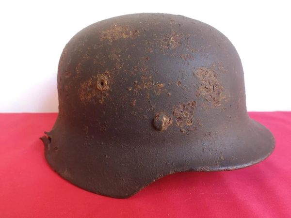 German soldiers M40 heavily damaged steel helmet with lots of green paint remains and decal clear to see it was recovered in the Demyansk Pocket near Leningrad in Russia 1941-1942
