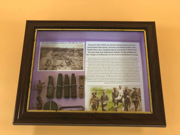 Glass framed group of relics all recovered in 2013 in the area that was Guillemont Station on the July-August 1916 battlefield on the famous Somme battlefield of 1916