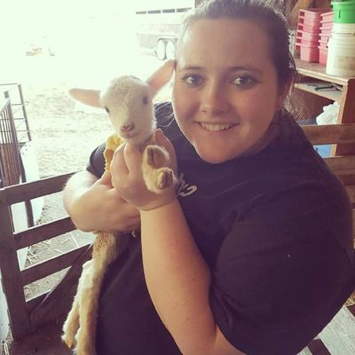 Maryellen on her home farm in Alberta Canada holding a baby lamb
