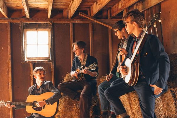 4 piece Bluegrass band sitting on bales of hay in a barn