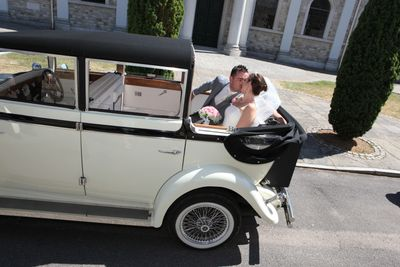 couple kissing in back of wedding car