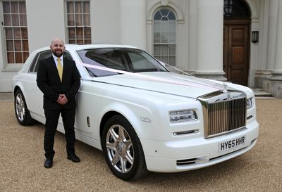 chauffeur standing next to a Rolls Royce