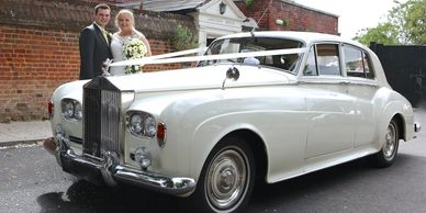 couple standing behind wedding car