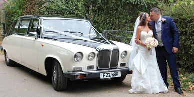 couple standing next to wedding car