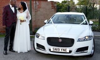bride+ groom standing next to new white Jaguar car