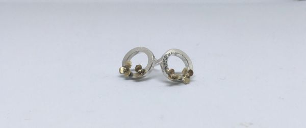 Silver circles decorated with tiny handcut gold flowers