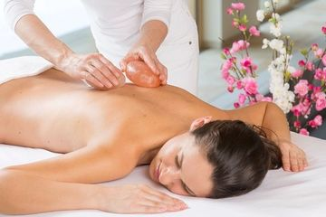 Classic white spa room, orchid flower background, Himalayan salt stones, gliding down woman's back,