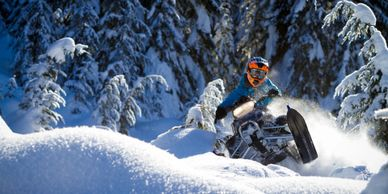 A rider enjoying a West Yellowstone snowmobile rental while powering through deep snow
