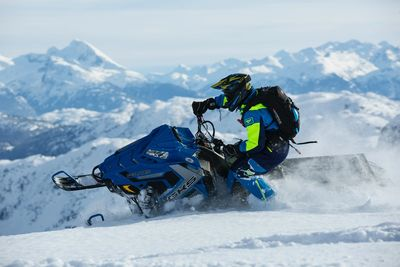 A rider enjoying a West Yellowstone snowmobile rental while turning sharply in the snow