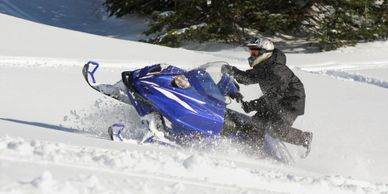 A rider enjoying a West Yellowstone snowmobile rental while climbing a steep hill in the snow