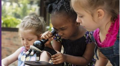 Three little girls, two of them are trying to look through a microscope