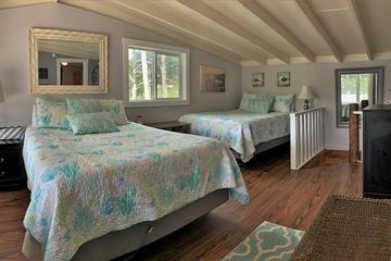 an interior view of a loft bedroom with two beds on the coast of Oregon