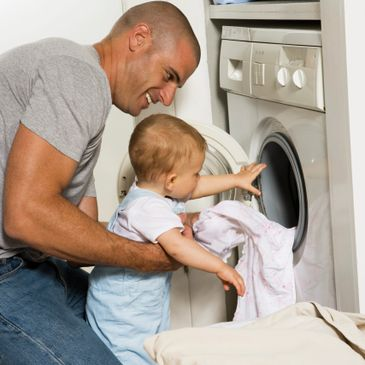 Dad and son in front of washer.