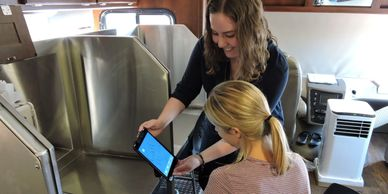 Enactus OC student demonstrating how to use an iPad installed in a mobile RV unit in Kelowna.