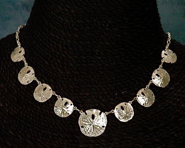 Sanddollar Collection. Featured is our necklace sanddollar piece, It is 1 large and 8 small pieces all gathered by our handmade link chain. Click here to see all the different sand dollar styles we offer.