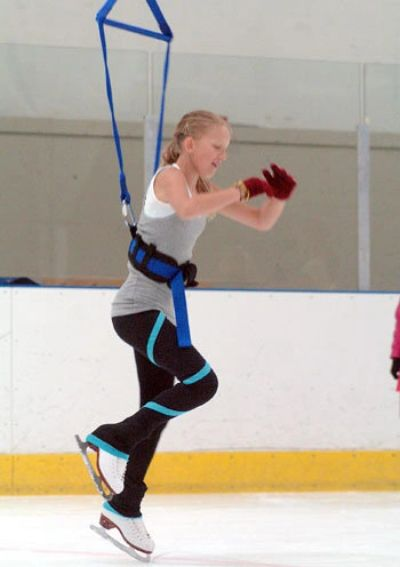 Ice skater in jump harness training system