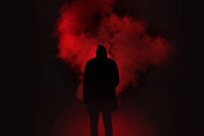 Human figure in the dark with red clouds behind  representing a threat that needs to be assessed.