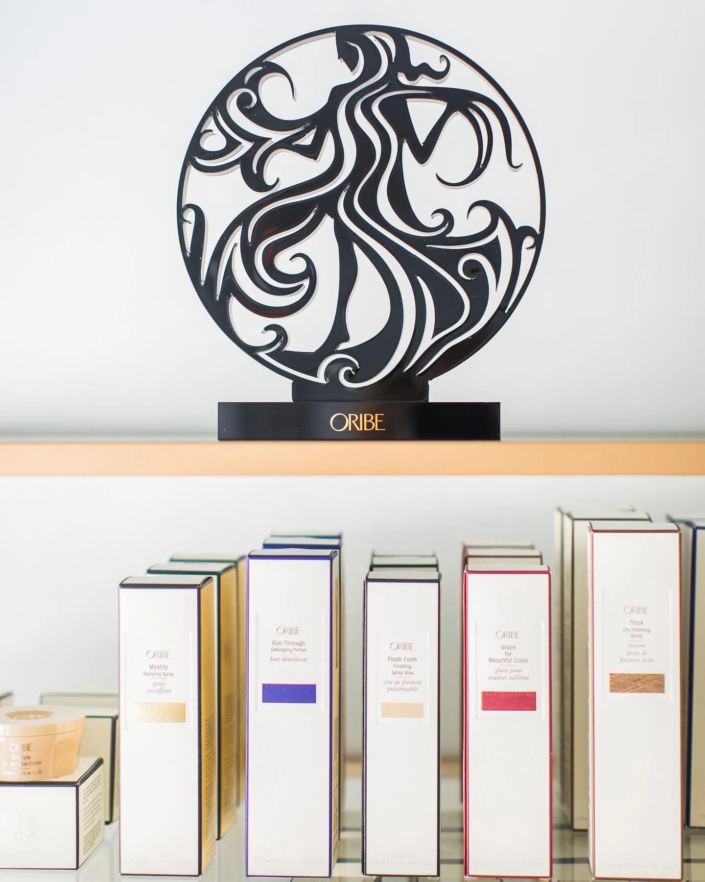 oribe logo on golden bookcase with salon products