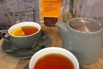 A cafe table with grey ceramic Forelife stump teapot and two cups of refreshing loose leaf Rooibos Chai Spices tea. The tea is deep orange in colour and is served with orange slices.