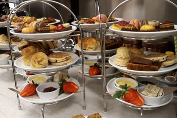 Three tiered cake stands ready to be served. Traditional Afternoon Tea, Plates filled with finger sandwiches, scones with jam & clotted cream, fresh strawberries, welsh cakes, home-made cakes, macaroons, and fancy cakes. One plate includes a selection of gluten free items.