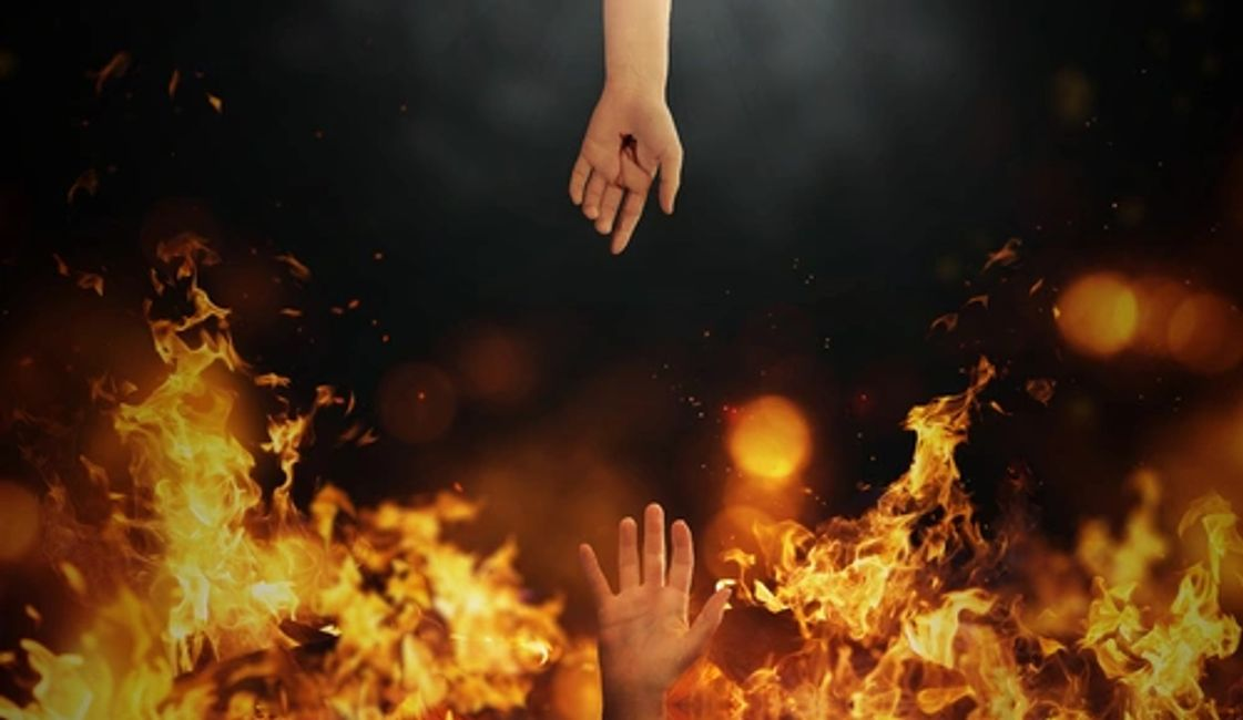 Jesus' Mercy meets God's Wrath; nail pierced hand reaching down to save someone from the fire