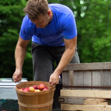Freedom's Edge co-founder Ned Ervin loading apples into his truck bed