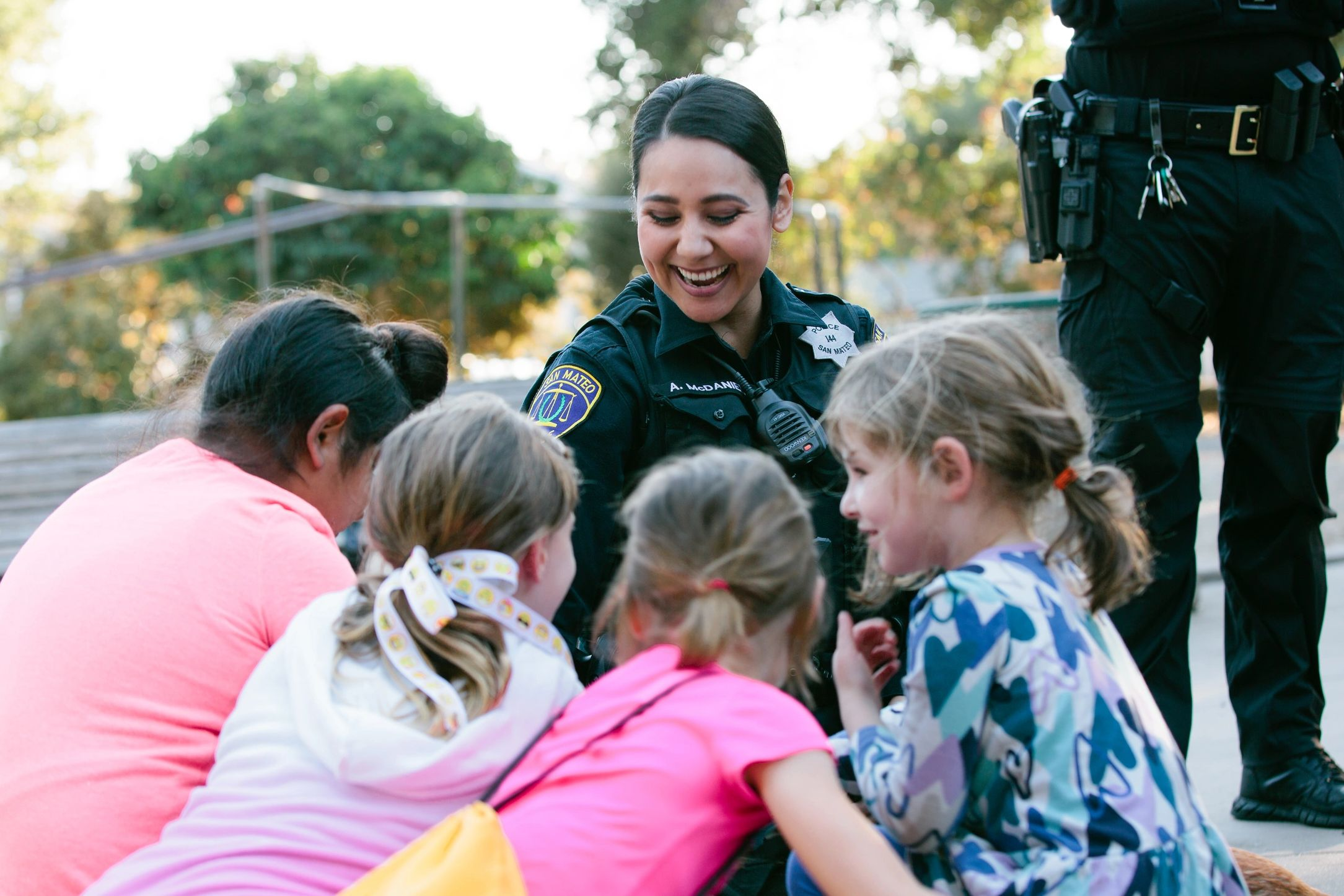 Police officers surrounded by children and a police canine.