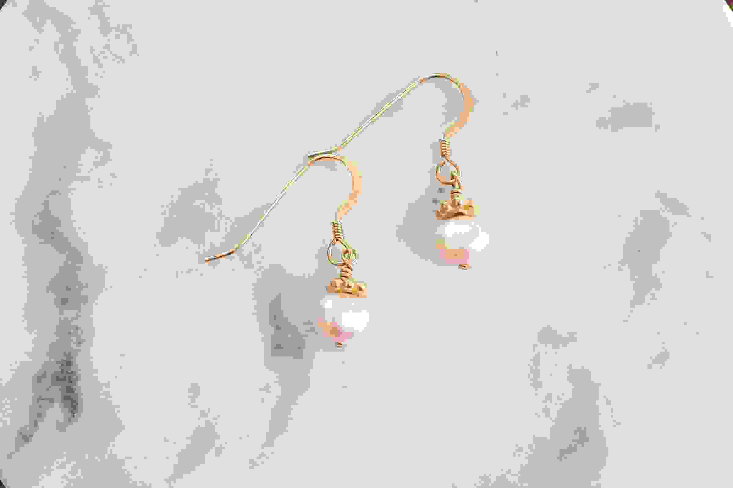 Light pink freshwater pearls and gold flower handmade earrings on white marble background.
