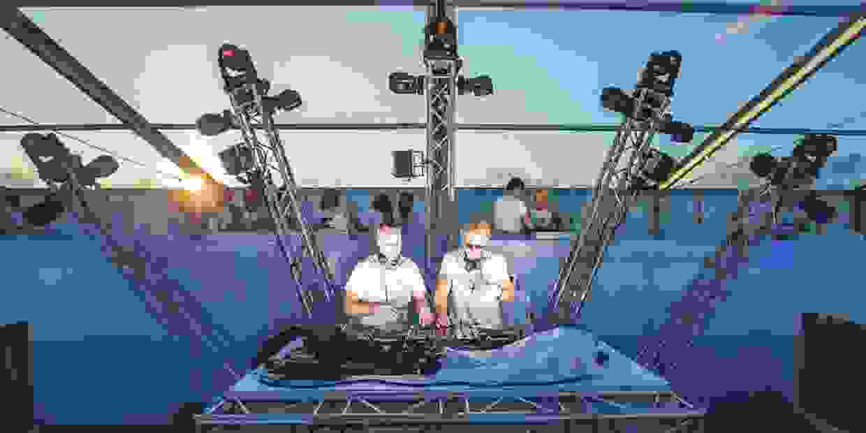 two disc jockeys on stage wearing white