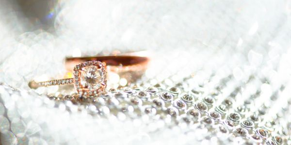 macro ring shoot on the wedding day of Diamonds and rose gold wedding rings on a sparkly background