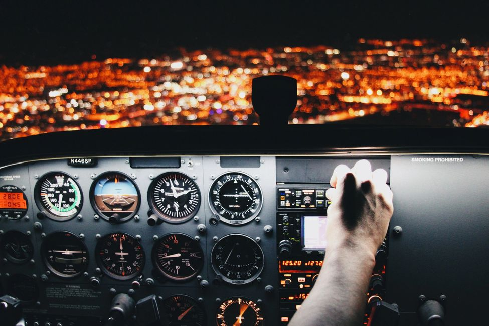 Cessna airplane cockpit with pilot adjusting knobs at night