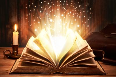 A candle and an open book full of sparklin