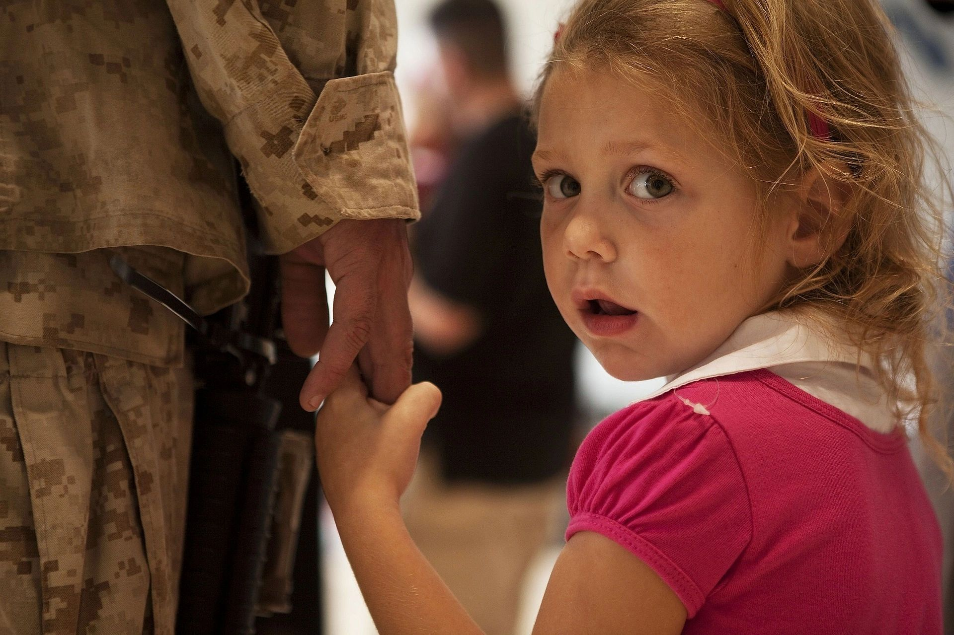 Little girl holds hand of father, a soldier