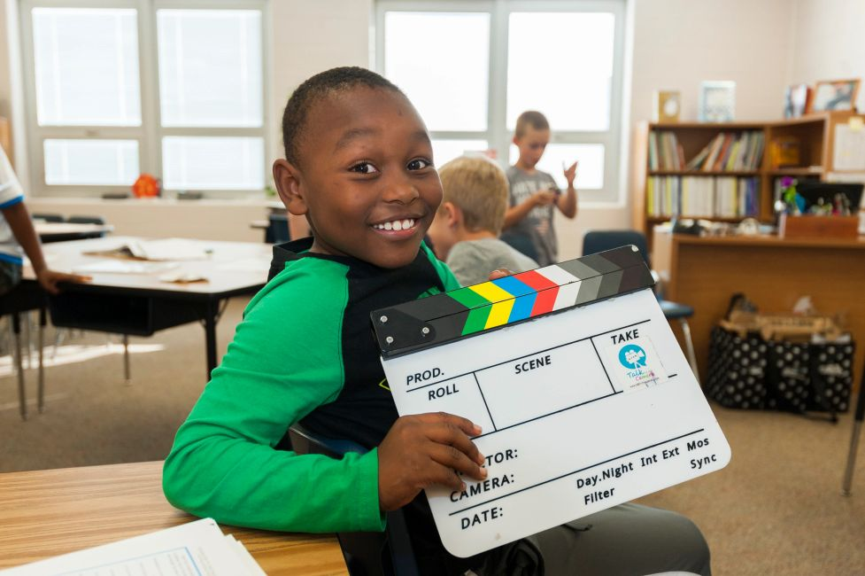 A young student in one of our movie magic classes, smiling at the camera with a clapboard in hand.