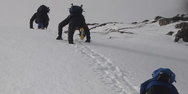 Kicking steps in the snow on a winter skills course.