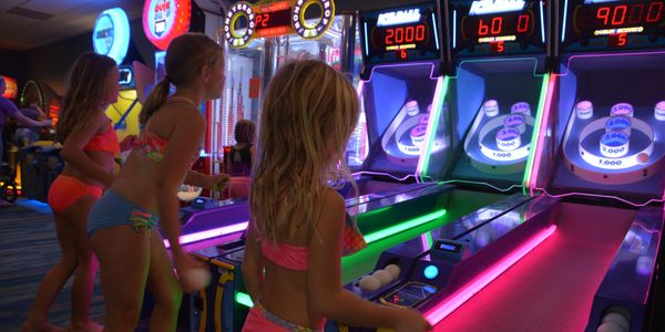 Girls playing Skee-Ball in the arcade
