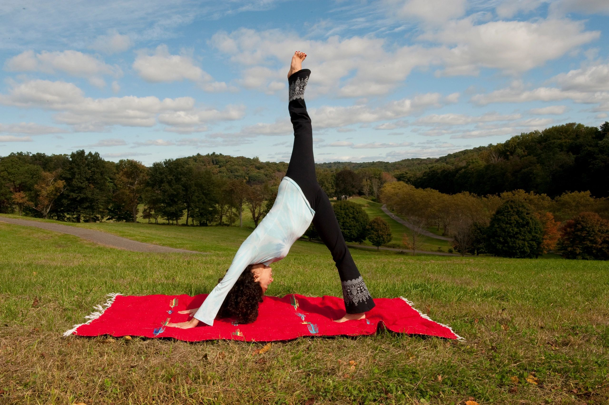 down dog split yoga pose outdoors under a blue sky