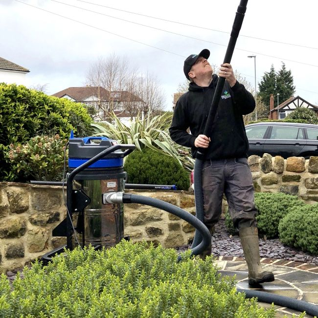 Cleaning gutters safely from ground level.
