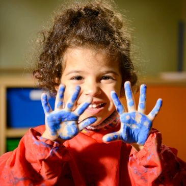 happy child showing blue painted hands Autism and ABA therapy in the Berkshires Massachusetts and Vermont Pittsfield Bennington Brattleboro Greenfield