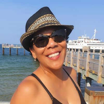 Smiling woman in hat and sunglasses at the marina