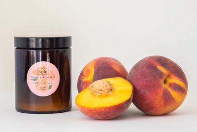 Peaches next to a peach fragranced soy candle.