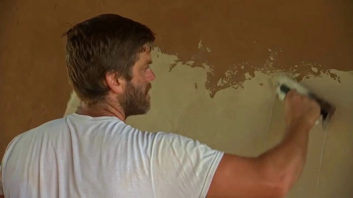 Our President, Ryan Runge, applying a clay plaster to a CEB wall